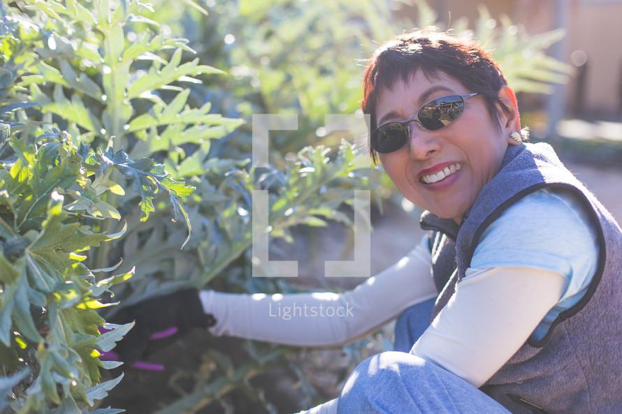 Smiling woman wearing sunglasses while gardening.