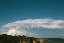 A huge cloud formation over a canyon.