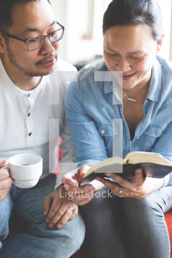 A man and woman reading a Bible