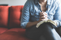 A woman reading a Bible and praying