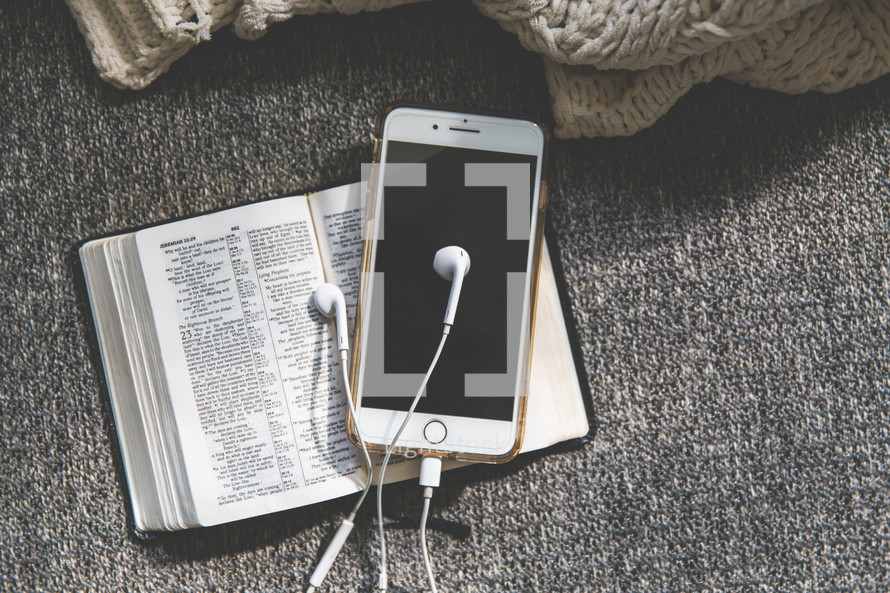 open Bible, earbuds, and cellphone on a couch
