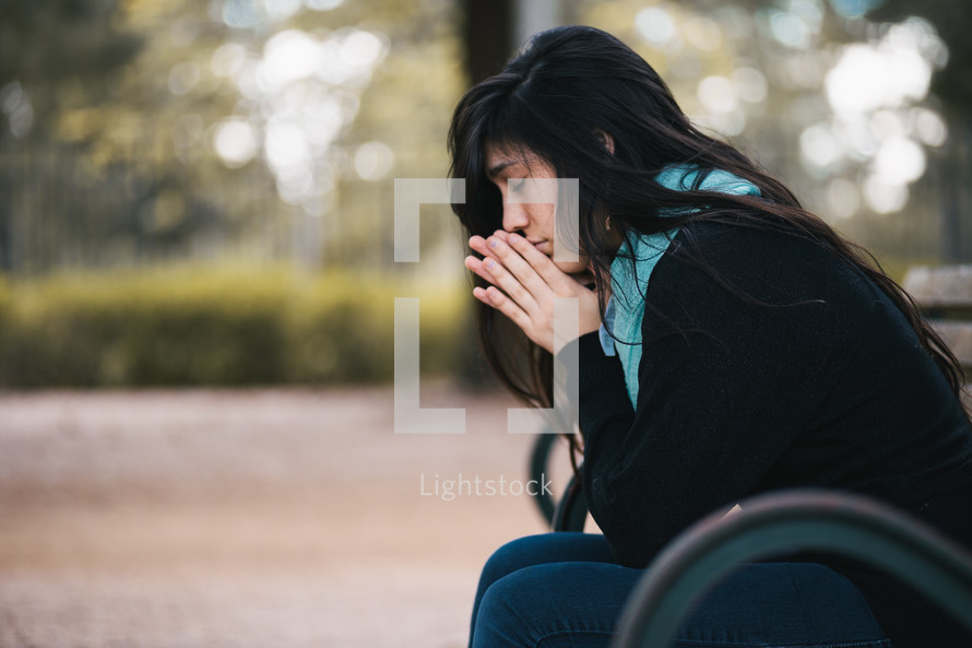 a woman in prayer sitting on a bench
