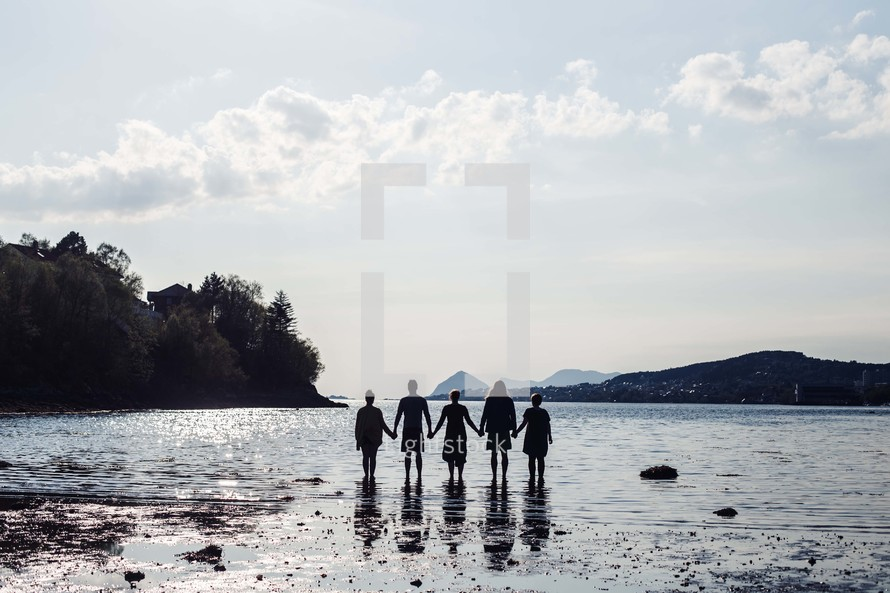 a family holding hands standing on a beach