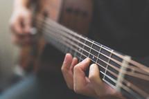 Hands strumming a guitar.