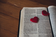 Candy hearts on the pages of a Bible.