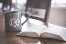 open Bible on a table and coffee mug at Christmas