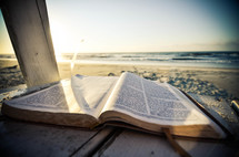 Open Bible on a wooden deck on the beach at the ocean.