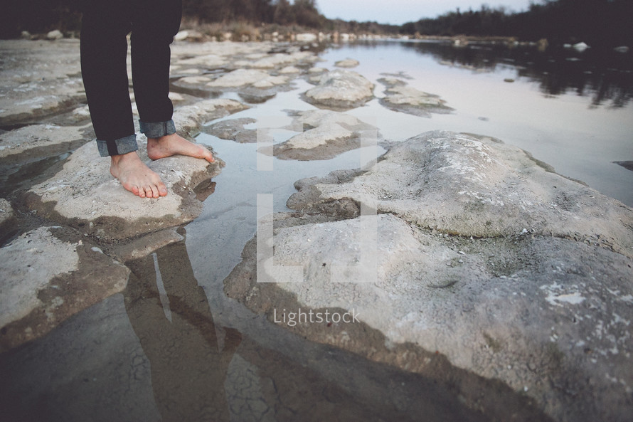 man's bare feet standing on rocks near a river