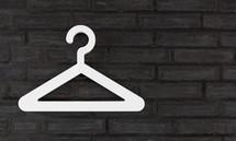 a single white hanger on black brick wall