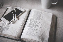 iphone and earbuds on an open Bible