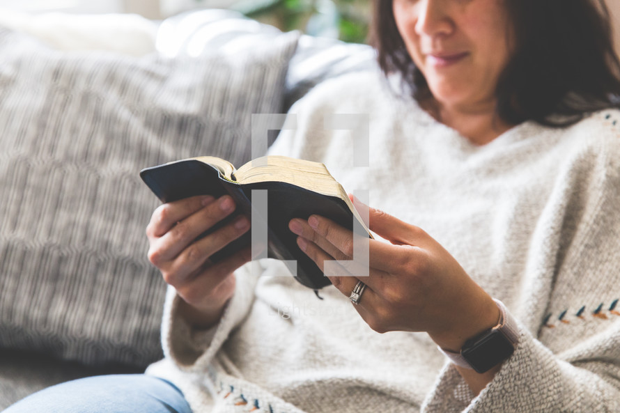 a woman sitting on a couch reading a Bible