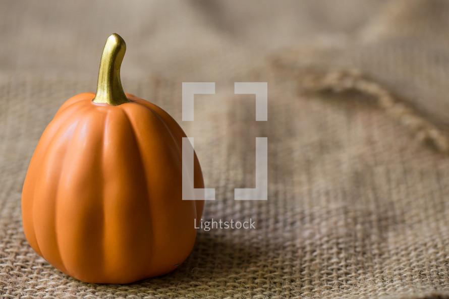 orange pumpkin on burlap