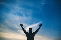 silhouette of a man with raised hands of worship
