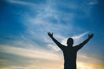 A silhouette of a man standing with hands raised in worship to God