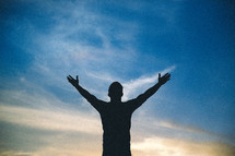 silhouette of a man with raised hands in worship to God