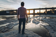 A man standing on a rocky shore looking out at the sun setting behind a bridge holding a Bible at his side