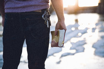A man standing holding a Bible at his side