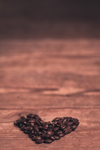 heart shaped coffee beans on wood background