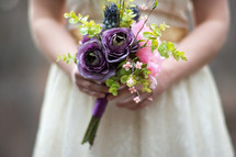 A young woman holding a bouquet of purple flowers.