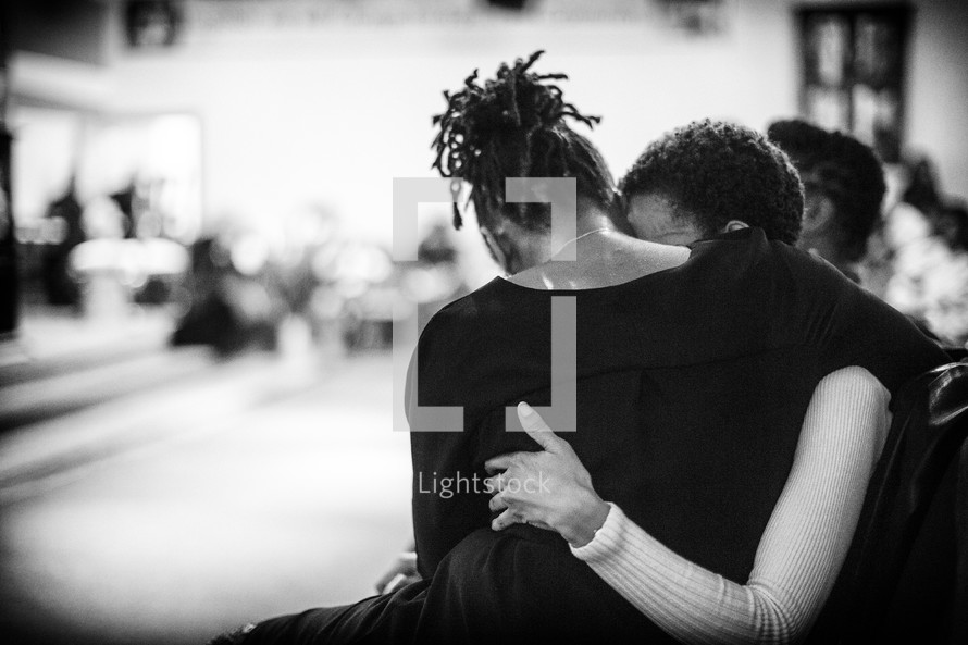 women hugging at church