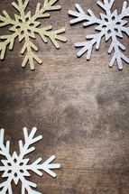 snowflake ornaments on a wood background
