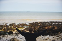 a man with raised hands standing on a shore