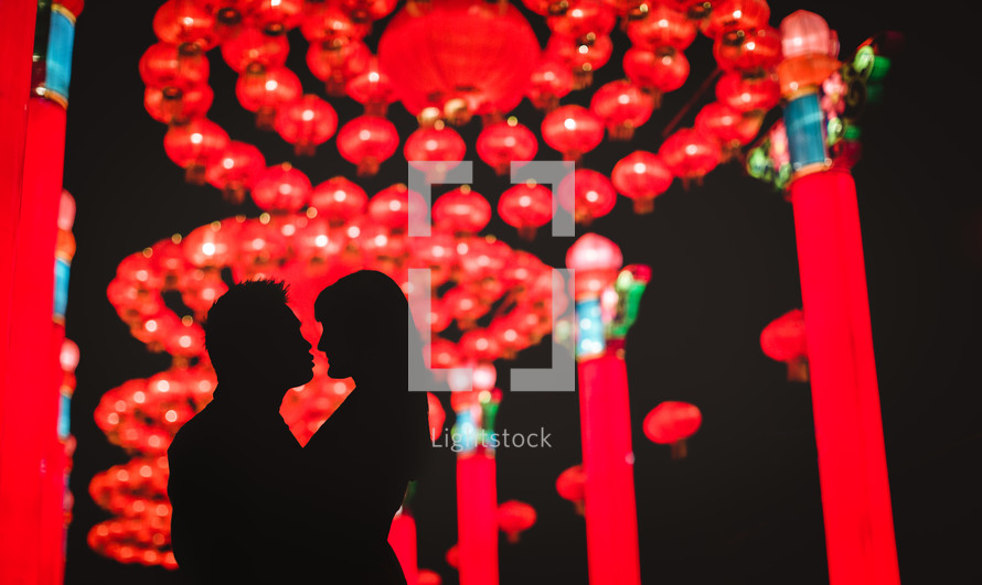 couple embracing under Chinese lanterns - decorations