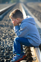 A little boy sits on a railroad track with his face in his hands.