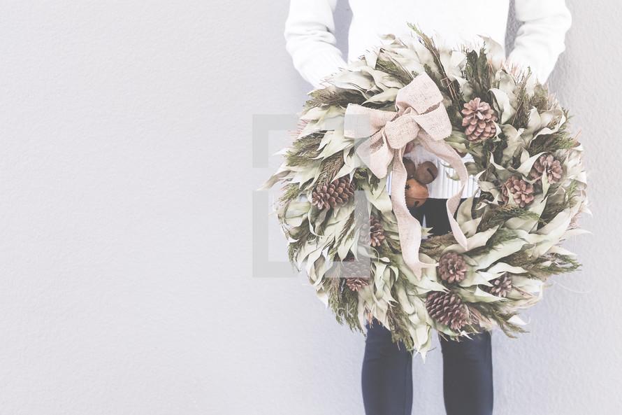 a woman holding a Christmas wreath