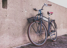 a bicycle leaning against a concrete wall