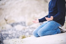 a man kneeling in prayer on a rocky shore