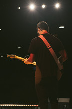 a man on stage holding a guitar