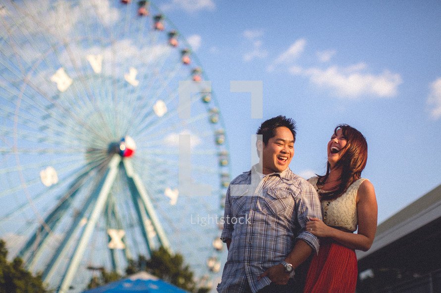 A couple laughing in front of a ferris wheel at the fair