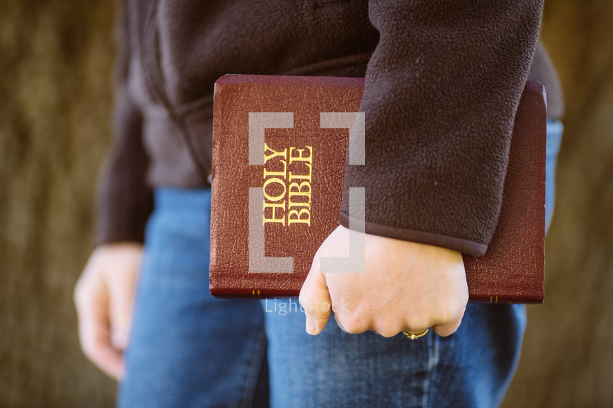 woman carrying a Bible at her side