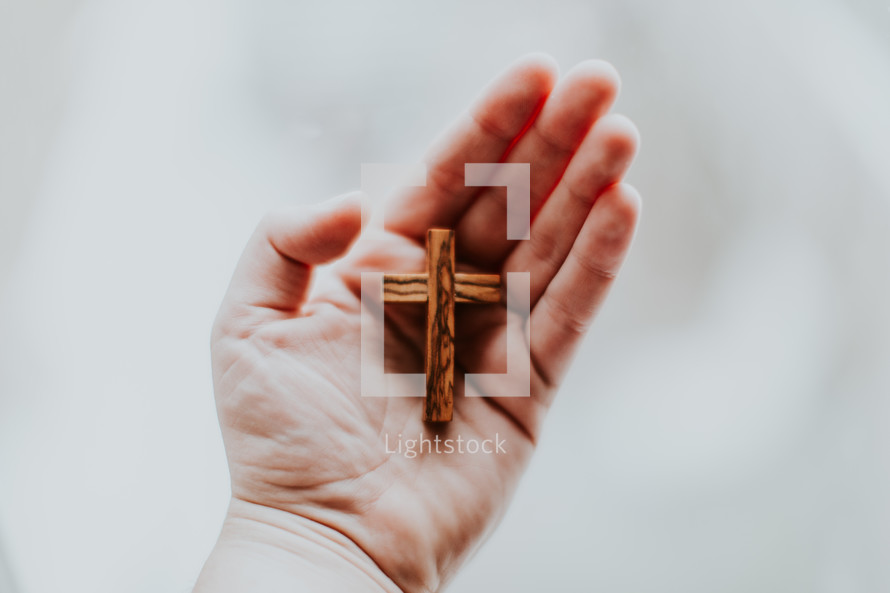 cupped hand holding a wooden cross