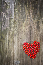 a heart of red berries on a wood background