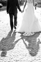 A bride and groom walk away holding hands.