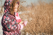 a girl child in a winter coat standing outdoors