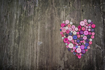 a heart of buttons on a wood background