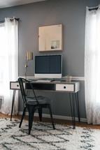 a computer desk between windows