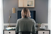 a woman sitting at a computer desk in a home office