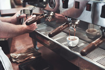 Hands operating espresso machine.