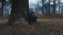 a woman sitting under a tree praying