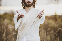Jesus standing in a field of tall brown grasses