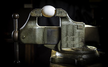 A small egg sweating in a large vise.