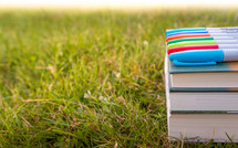 sharpies on a stack of books in the grass