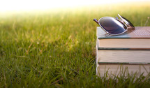 sunglasses on a stack of books in the grass