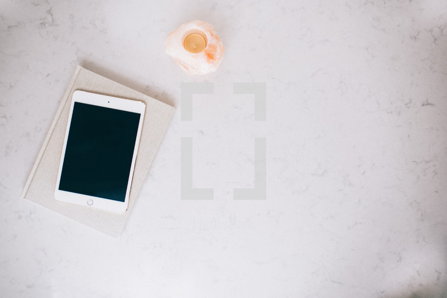 iPad, book, and candle