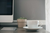 a cup and saucer on a desk in front of a computer screen