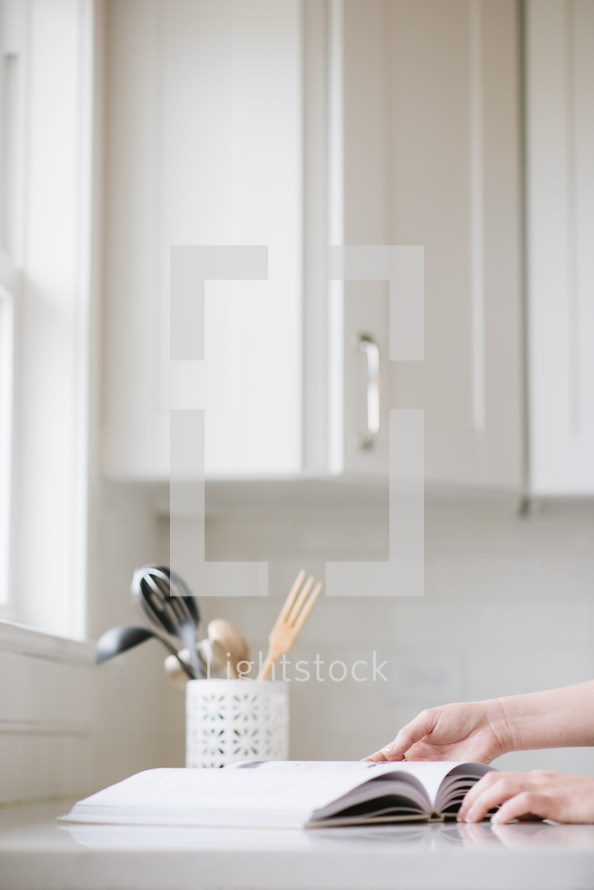 a woman flipping through the pages of a cookbook